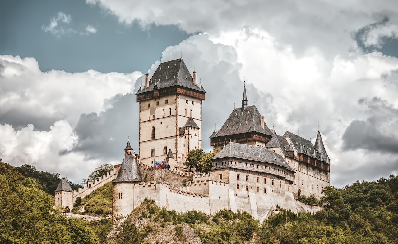 Complete view of Karlstejn castle on hill surrounded by forest
