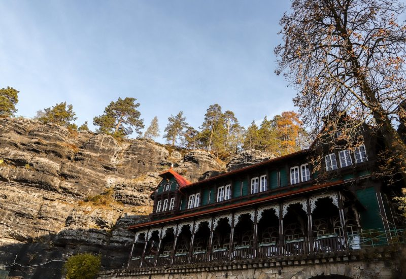 Wooden touristic restaurant under rock formations on Bohemian Switzerland national park day trip