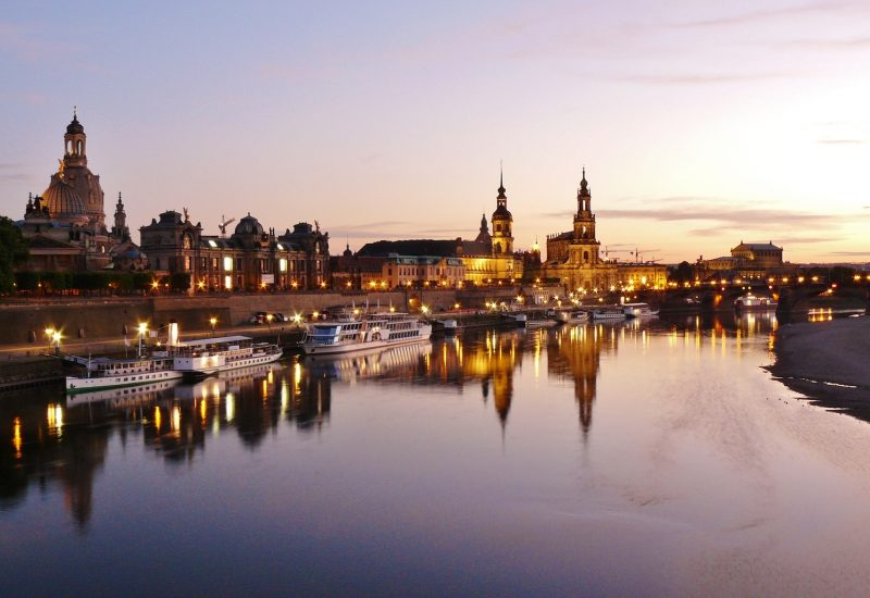 Dresden Old Town at night with boats on Elbe river