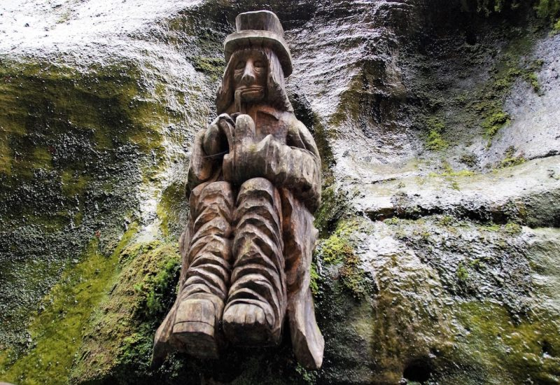 Wooden statue of waterman with pipe sitting on rock